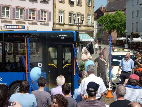 Stadtbus wird über eine Sprenkelanlage getauft.