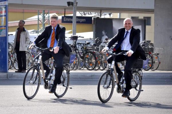 Stadtwerke Geschäftsführer Gerd Hertle und Oberbürgermeister Stefan Schlatterer fahren nebeneinander auf den Elektro-Fahrrädern.