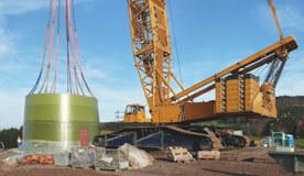 Kran setzt Fundament für die Windkraftanlage