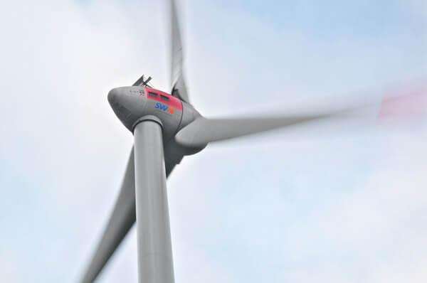 Gondel der Windkraftanlage mit dynamisch drehenden Rotorblättern.