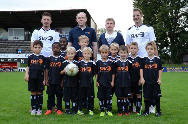 Oliver Westhäußer (Trainer), Thomas Schneider (Vertriebstleiter der SWE), Sven Meyer (PRO FCE) und Dominik Falk (Trainer) und die Nachwuchskicker des FCE in ihren neuen Trikots.