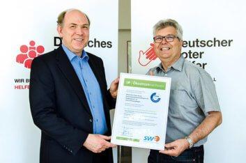 Thomes Schneider (SWE-Vertriebsleiter) übergibt Roland Heß (stellv. Kreisgeschäftsführer DRK) den Nachweis zur TÜV NORD-geprüften Ökostromlieferung.