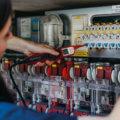 Auszubildende überprüft Widerstände der Sicherungen in Stromkasten