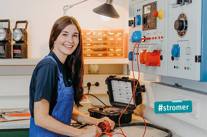 Auszubildende als Elektronikerin überprüft Kabel mit Prüfstation
