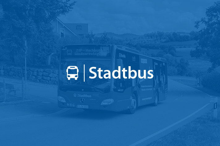 Schriftzug Stadtbus steht vor einem fahrenden Stadtbus
