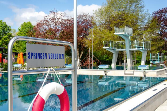 Foto: Im Vordergrund steht das Schild: Springen verboten. Im Hintergrund ist ein Teil des Schwimmerbeckens und der 5-Meter Sprungturm zu sehen.