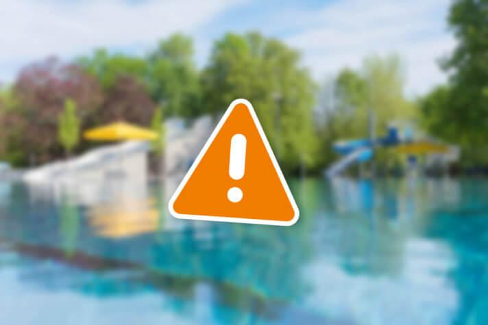 Ausrufezeichen vor orangen Dreieck. Im Hintergrund ein verschwommenes Foto des Freibads.