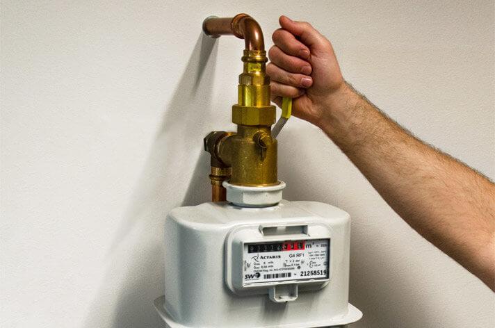 Hand öffnet ein Ventil eines Erdgas-Zählers