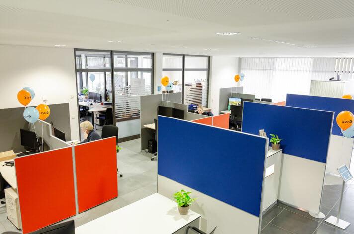Foto des modernisierten Kundencenters. Orangene und Blaue Stellwände trennen die verschiedenen Bereiche