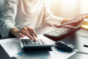 Vor dem Computer sitzende Frau tippt mit Kugelschreiber in der Hand in den Taschenrechner.