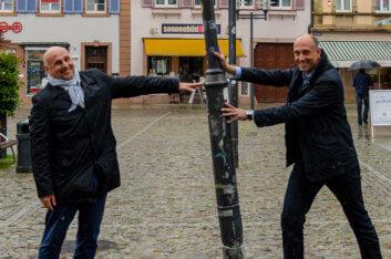 Bürgermeister Schlatterer und Stadtwerke-Chef Michel stützen eine schiefe Lampe auf dem Marktplatz.