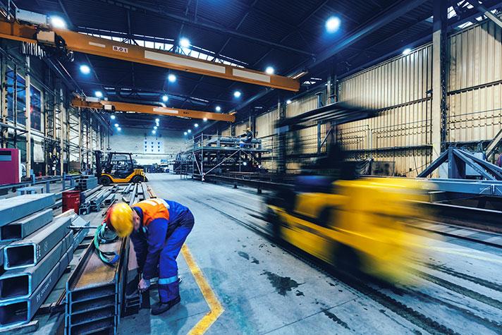 Gabelstapler fährt dynamisch durch eine Fabrikhalle
