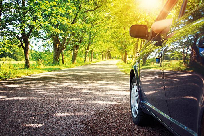 Auto fährt durch grüne Landschaft