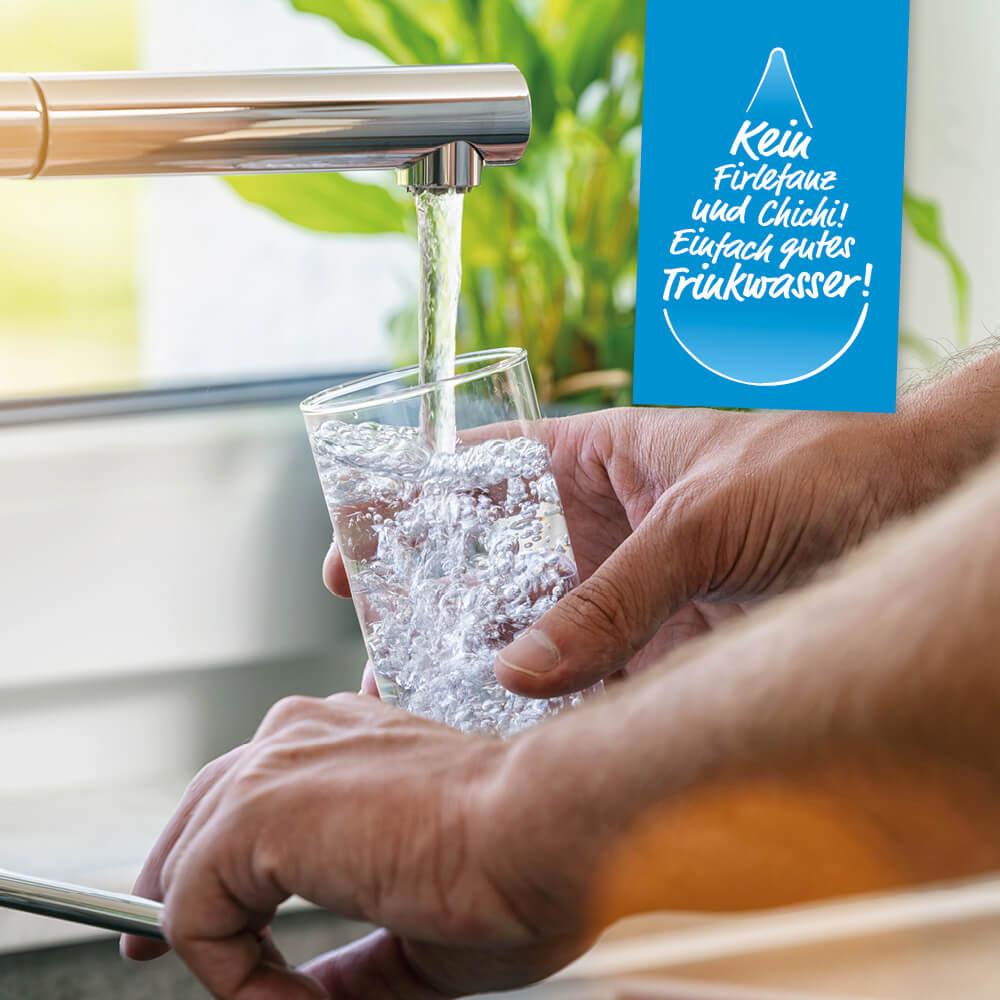 Ein Mann füllt ein Glas mit Leitungswasser unter dem Wasserhahn.