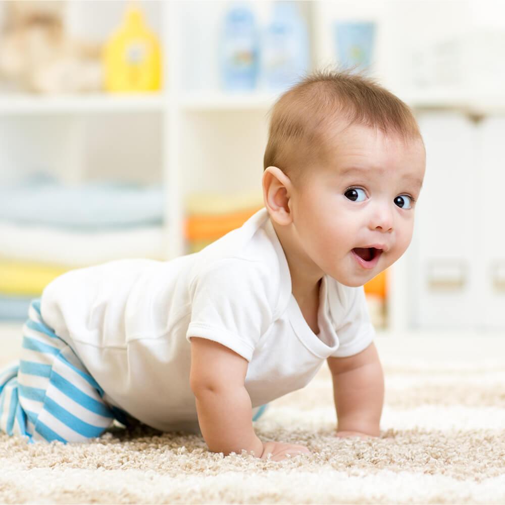 Ein Baby krabbelt auf einem weißen Teppich.