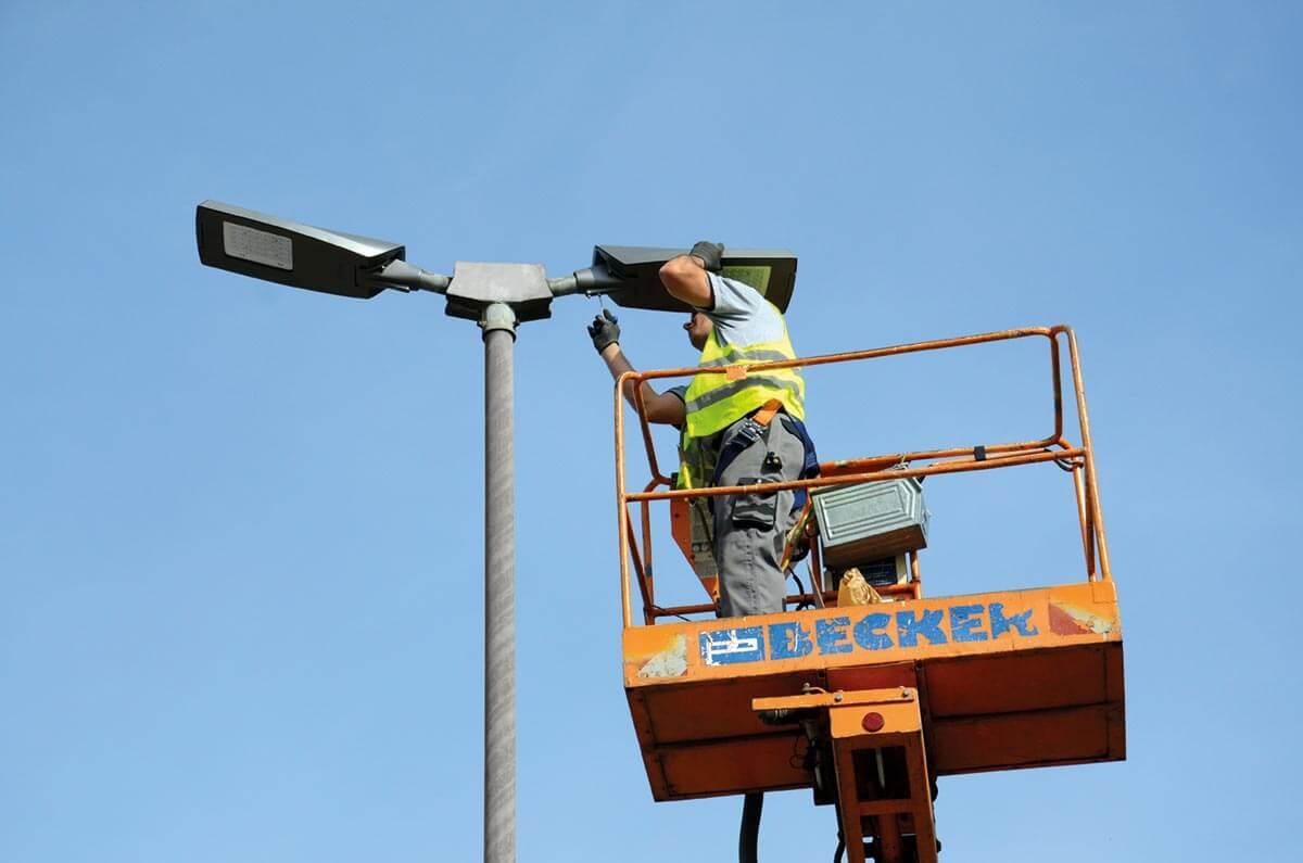 Techniker schraubt an Lampe einer Laterne.