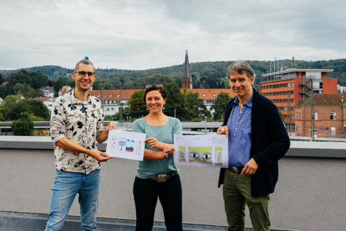 Oli Lou Kramer, Christine Rötzer und Günther Hoffmann präsentieren die Sieger-Designs des Kunstwettbewerbs.